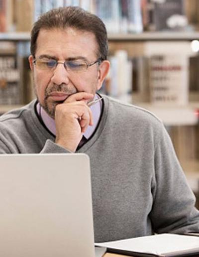 Decorative picture of an adult man on a computer.